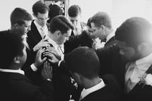 groomsmen and groom in prayer before a wedding
