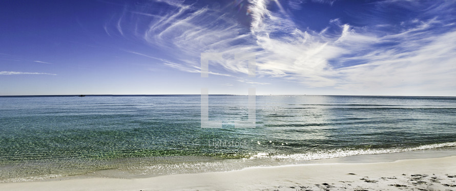 wispy clouds over clear blue green ocean water