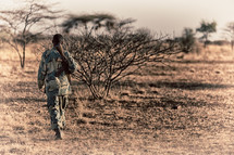 a soldier carrying a rifle in Africa