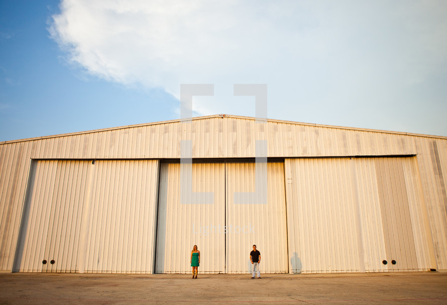 man and woman standing in front of a warehouse