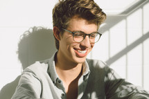 smiling face of a young man in reading glasses