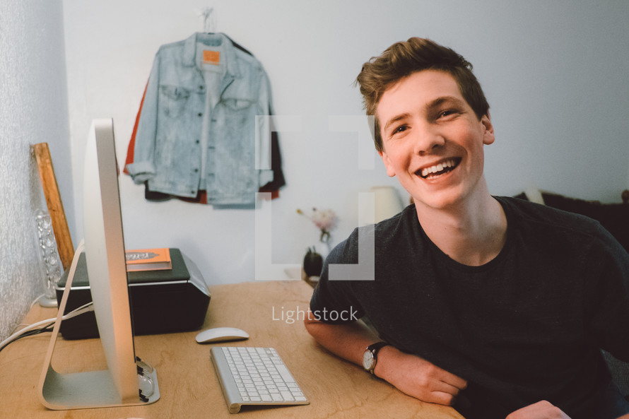 smiling face of a young man sitting at a computer desk