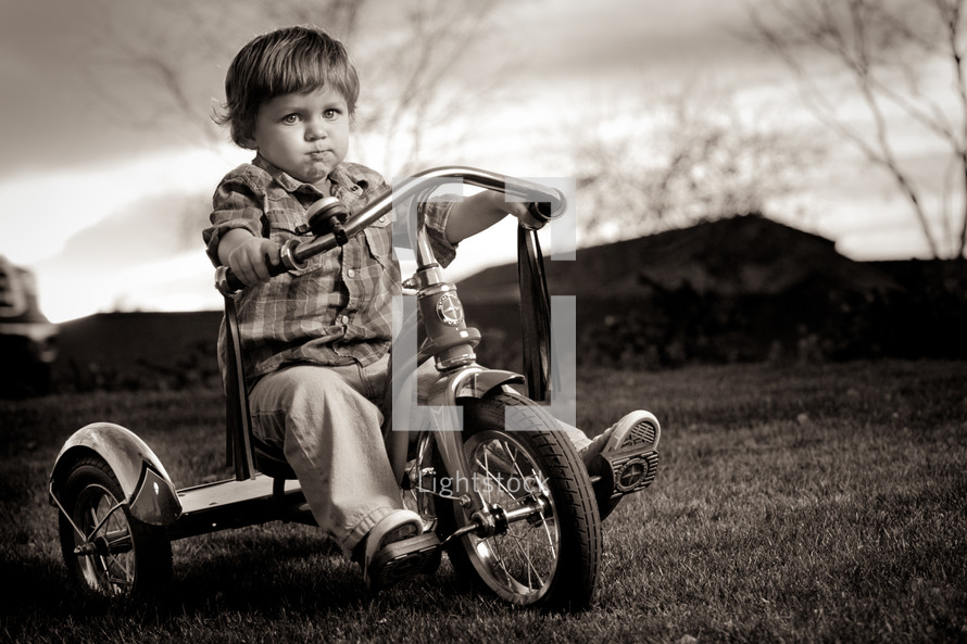 toddler boy riding a tricycle