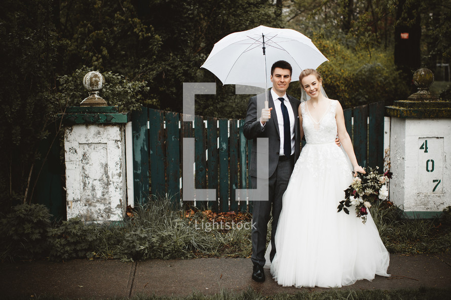 bride and groom with an umbrella