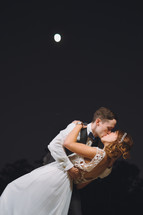 bride and groom kissing under a full moon
