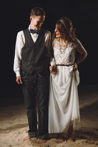 bride and groom standing in stand on a beach at night
