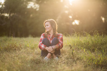 woman wearing a plaid shirt sitting in grass