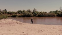 a man walking to be baptised in a river