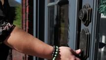 hand opening a front door