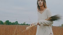 a woman walking through a field carrying a sheath of wheat