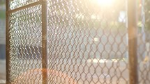 Sunshine through a chain link fence at a baseball field.