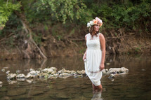 woman in a white dress and flowers in her hair walking in water
