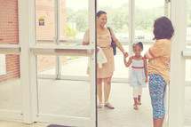 a greeter welcoming a mother and daughter