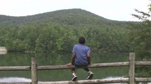 a child looking out at mountains and a lake