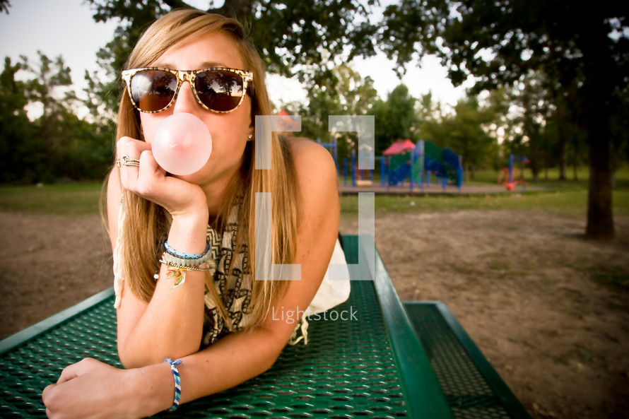 teen lying on top of a table blowing a bubble