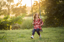 Teen girl on a swing outside.