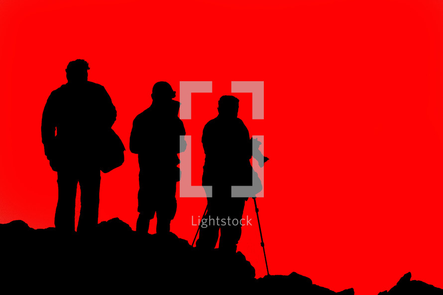 silhouettes of tourists in front of a red sky
