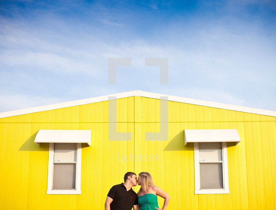 man and woman kissing in front of a yellow house