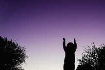 silhouette of a child with raised hands at sunset