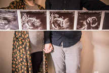mother and father holding ultrasound pictures