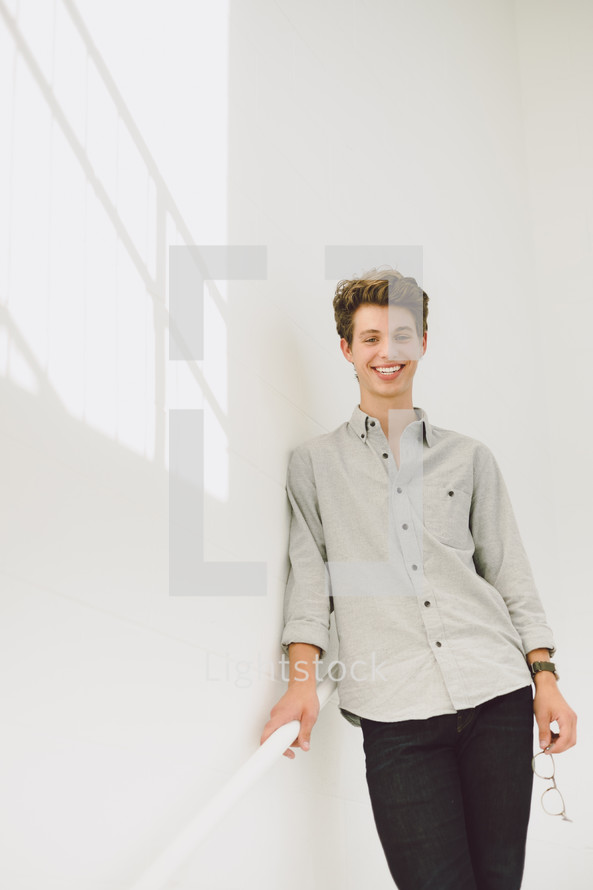 smiling young man holding onto a stair railing