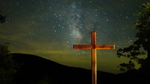 Timelapse of star and cloud movement over a cross on a hill.