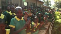 school children clapping hands and singing outdoors