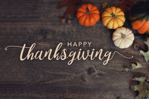 Happy Thanksgiving Typography Over Dark Wood Background with Pumpkins and Leaves