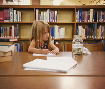 a child in a library doing homework next to a jar for education funds