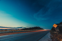 Headlights of highway traffic at sunset.