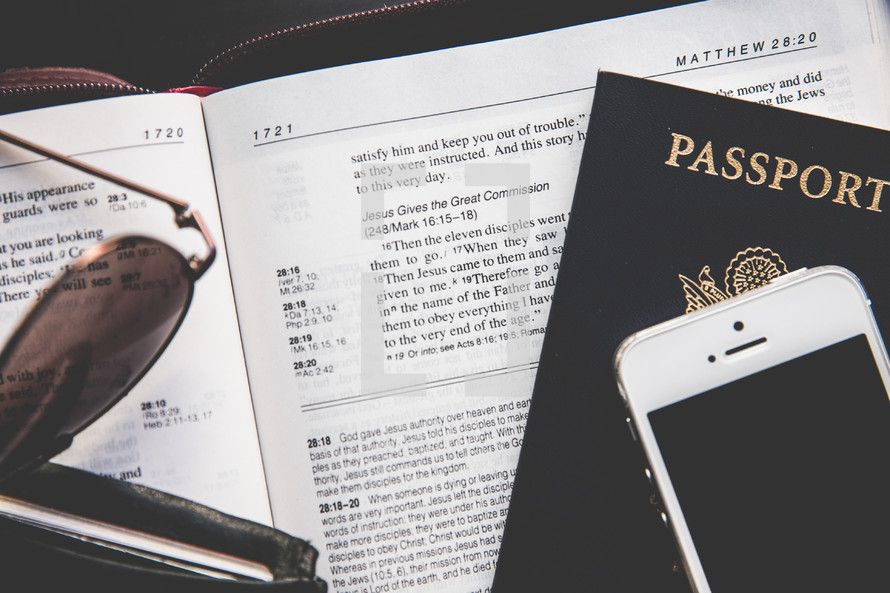 Bible, wallet, passport, sunglasses, and iPhone on a table
