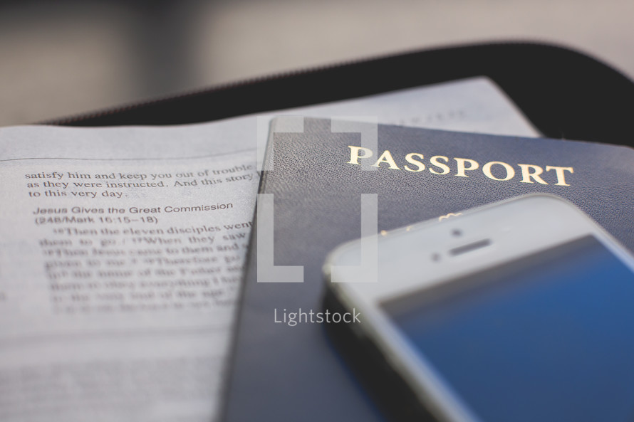 an iPhone, passport, and open Bible