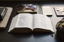 wallet, journal, open Bible, pen, coins, bag, iPhone, sunglasses, and passport on a table