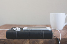 an iPhone and earbuds on a Bible and a coffee mug