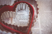 Heart shaped cookie cutters on the pages of a Bible.