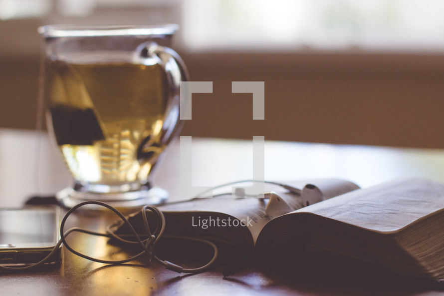 iphone, ear buds, tea, mug, and a Bible