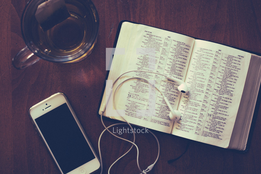 iphone, ear buds, tea, and a Bible