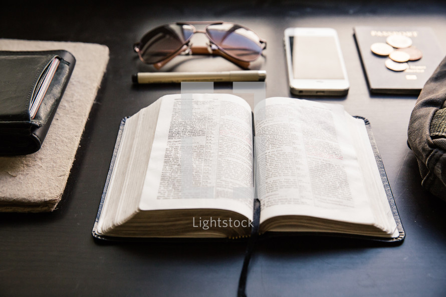 Bible, wallet, passport, sunglasses, pen, iPhone, and journal on a table