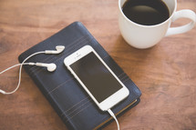 on iPhone and earbuds on a Bible and a coffee mug