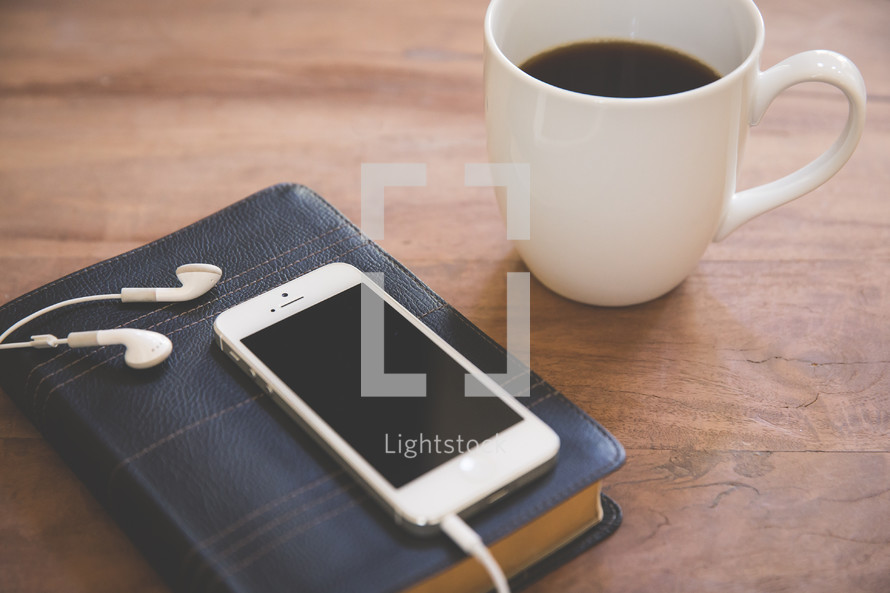iPhone and earbuds on a Bible and a coffee mug
