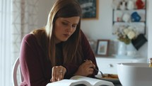 a woman reading a Bible at home