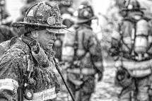 Firemen covered in soot.