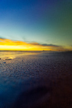sunset over wet sand on a beach