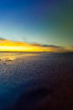 sunset over wet sand on a beach