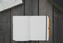blank pages of an open journal, map, and personal speaker on wood background