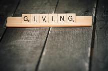 """""""Giving"""" spelled in Scrabble tiles."""