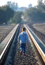 boy child walking alone on train tracks