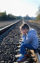 boy child sitting alone on railroad tracks