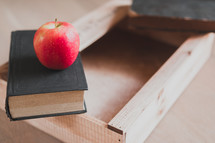 apple, book, and wooden tray