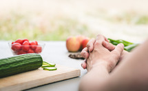 a man praying in front of vegetables on a cutting board